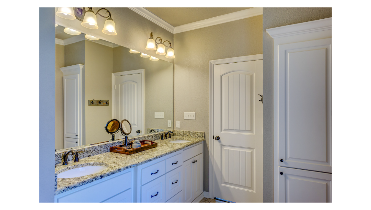 photo of a clean master bathroom with white cabinets, brown-toned countertop, and double-sinks