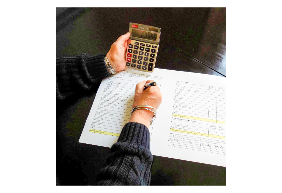 Woman with a calculator planning her monthly budget